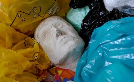 Ihmisen päätä esittävä kipsiveistos muovipussien seassa.