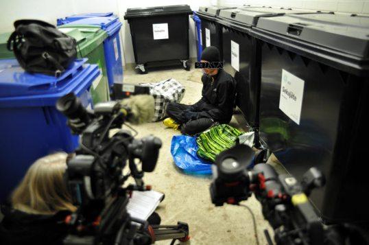 Onni Tonkija jätehuoneen lattialla kahden videokameran ja haastattelijan edessä.