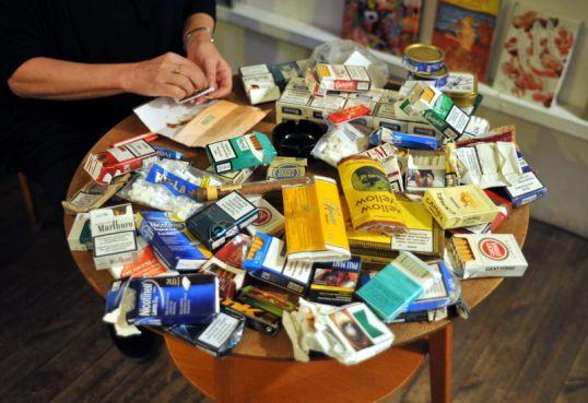 Kädet lisäämässä irtotupakkaa kääreeseen. Pyöreällä pöydällä lisäksi tupakka-askeja ja -toppia, sätkäpaperipakkauksia, filttereitä, nuuskapurkkeja, purukumipaketteja sekä sikari ja tuhkakuppi.