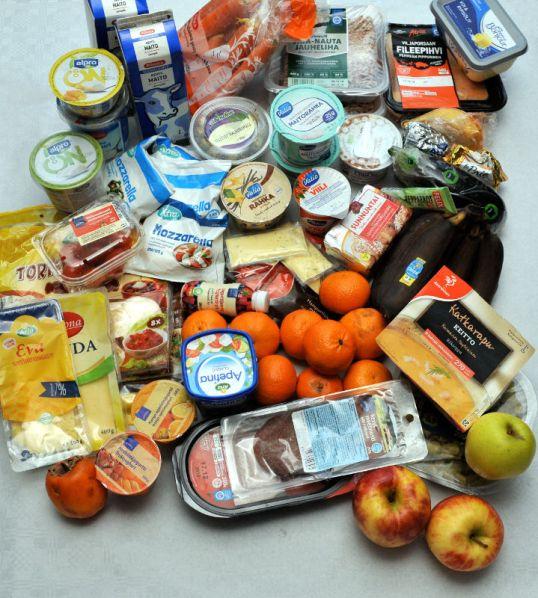 Vaalealla alustalla muun muassa hedelmiä, juusto- ja leikkelepakkauksia, rahka- ja jukurttipurkkeja, lihapaketteja ja maitotölkkejä.