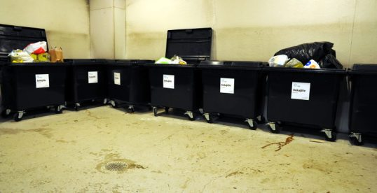 Mustia, roskapusseja pursuavia sekajäteastioita jätehuoneessa.