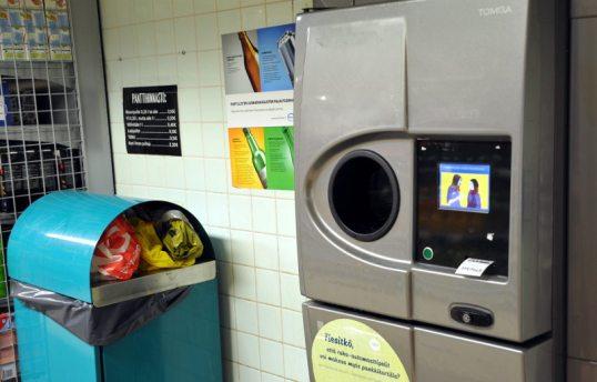 Pullonpalautusautomaatti, jonka vieressä on roska-astia täynnä muovikasseja.