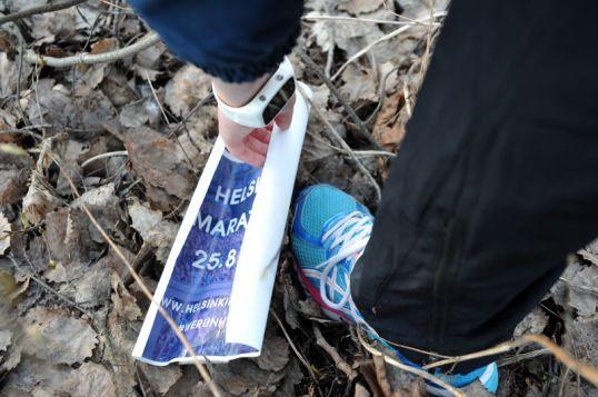 Lenkkeilijä poimii mainosjulisteen maahan pudonneiden lehtien päältä.