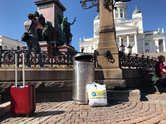 Valkoinen muovikassi Senaatintorilla roskakorin vieressä. Taustalla Helsingin tuomiokirkko.