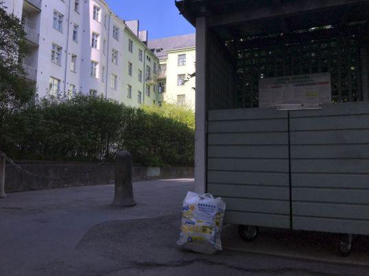 Valkoinen muovikassi nojaa jätekatokseen Sonckin korttelissa.