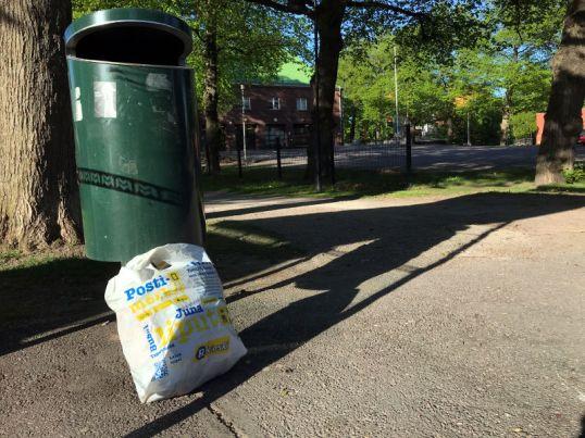 Valkoinen muovikassi roskakorin vieressä Käpylän pelastusaseman edessä.