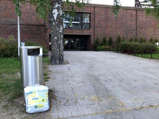Valkoinen muovikassi roskakorin vieressä Oulunkylän kirkon edessä.