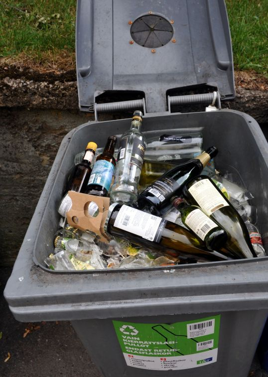 Harmaassa muovisessa 240 litran kierrätyslasipulloastiassa lasinsirpaleita ja lasipulloja.