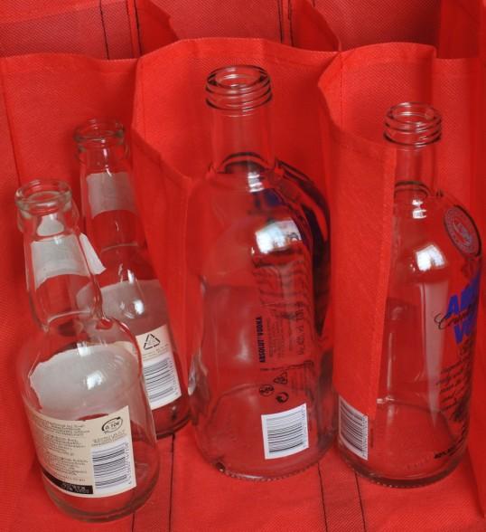 Punaisessa, lokeroidussa pullokassissa kaksi pientä siideripulloa ja kaksi isoa votkapulloa.