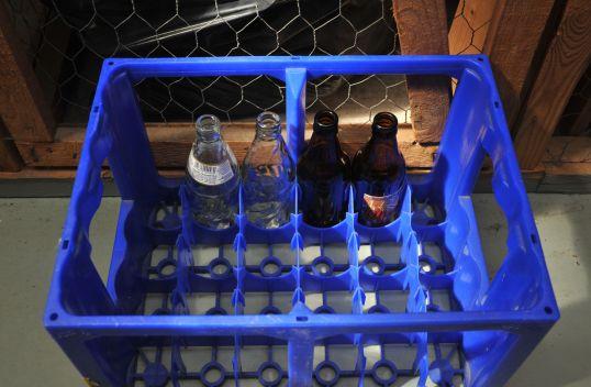 Häkkikomeron oven edessä sininen olutkori, jossa on lasiset kaksi 0,3 litran kirkasta virvoitusjuomapulloa ja kaksi 0,33 litran ruskeaa olutpulloa.