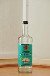 Tyhjä Berliner Luft -liköörin kirkas 1,0 litran pullo puunvärisellä lattialla.