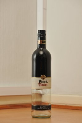 Tyhjä Black Tower -valkoviinin kaksivärinen 0,75 litran lasipullo puunvärisellä lattialla.