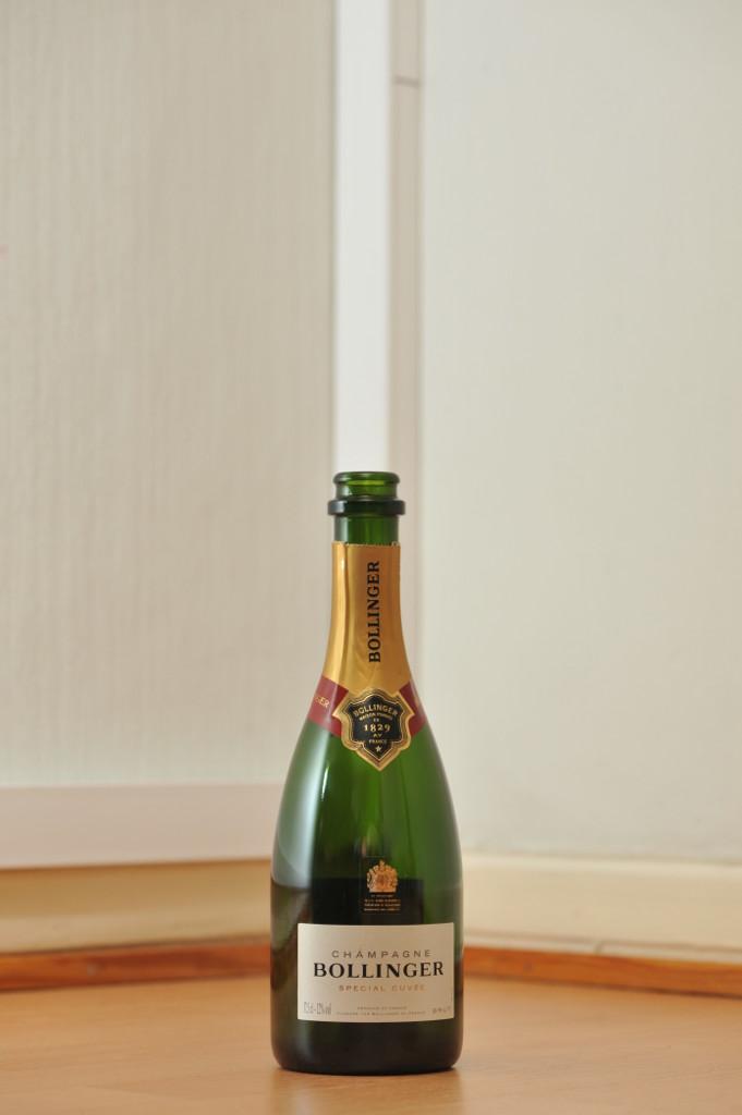 Tyhjä Bollinger-samppanjan 0,375 litran vihreä lasipullo puunvärisellä lattialla.