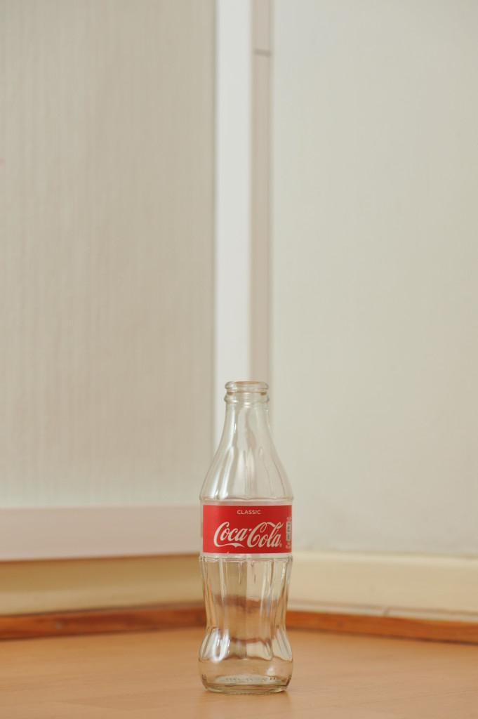 Tyhjä lasinen 0,25 litran Coca-Cola-pullo puunvärisellä lattialla.