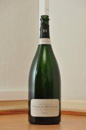 Tyhjä Franck Bonville -samppanjan 1,5 litran vihreä lasipullo puunvärisellä lattialla.