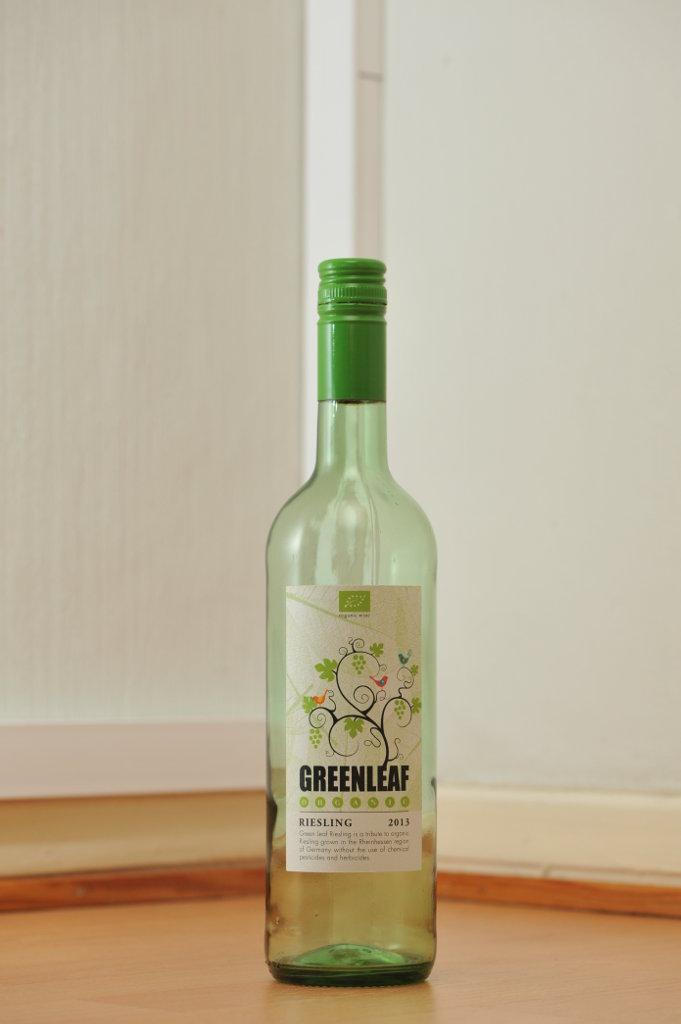 Tyhjä Greenleaf-valkoviinin kirkas, vihertävä 0,75 litran lasipullo puunvärisellä lattialla.