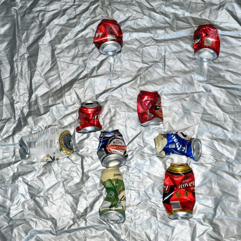 9 puristunutta juomatölkkiä hopeanvärisen peitteen päällä.