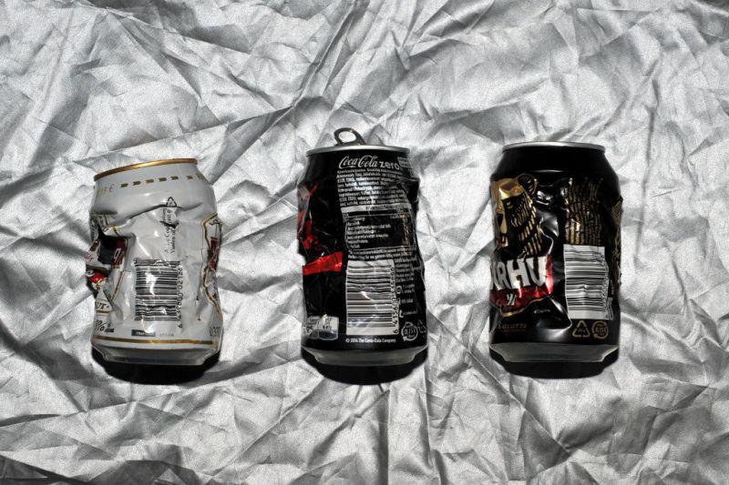 Kolme lommoista juomatölkkiä hopeanvärisen peitteen päällä.
