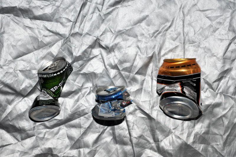 Kolme kiertyneesti rutistunutta juomatölkkiä hopeanvärisen peitteen päällä.