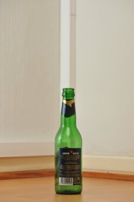 Tyhjä Lapin Kulta -oluen vihreä 0,33 litran lasipullo puunvärisellä lattialla.