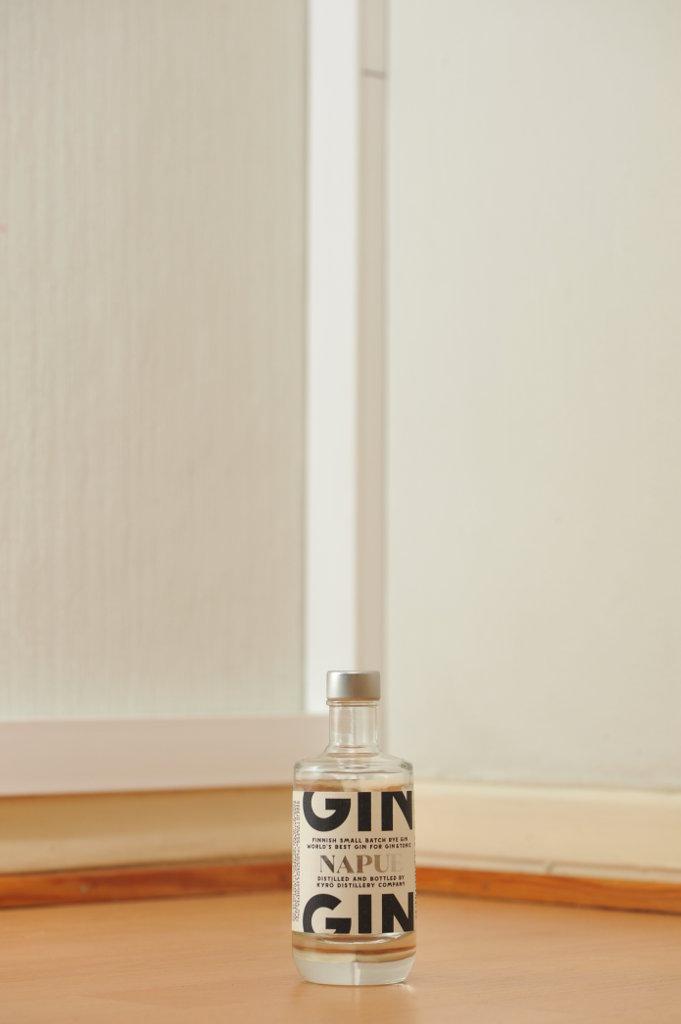 Tyhjä Napue-ginin 0,10 litran kirkas lasipullo puunvärisellä lattialla.