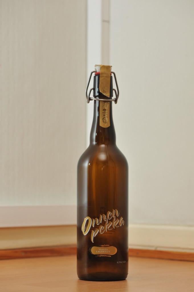 Tyhjä Onnenpekka-oluen 0,75 litran ruskea patenttikorkkipullo puunvärisellä lattialla.