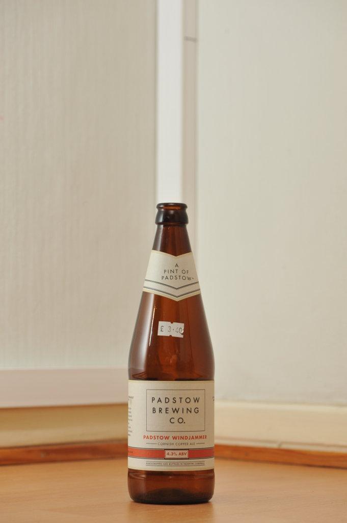 Tyhjä Padstow-oluen 0,568 litran ruskea lasipullo puunvärisellä lattialla.