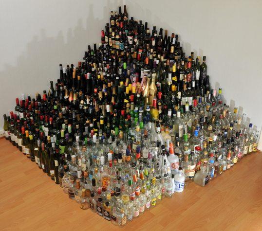 Lattialta nouseva, nurkkaan rajautuva noin 600 pullosta muodostuva pyramidi. Kirkkaat pullot edessä, tummat takana.