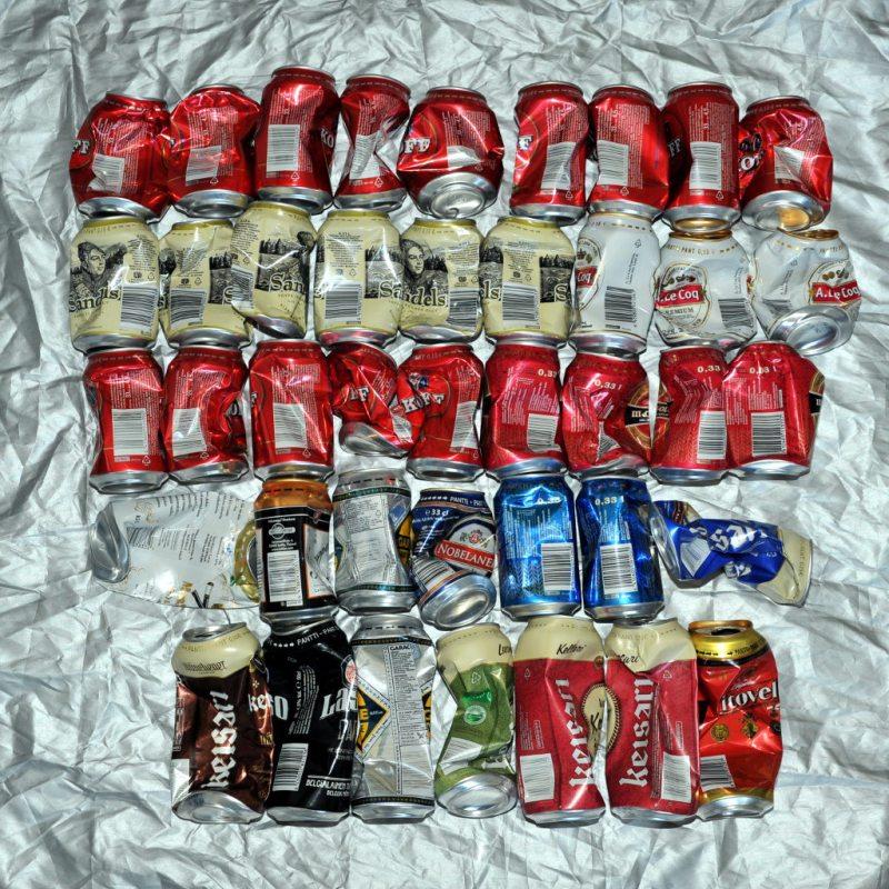 41 puristunutta juomatölkkiä hopeanvärisen peitteen päällä.