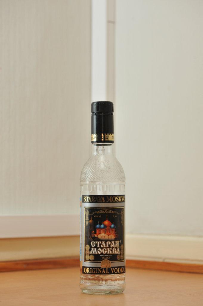 Tyhjä Staraja Moskva (Старая Москва) -votkan 0,5 litran kirkas lasipullo puunvärisellä lattialla.