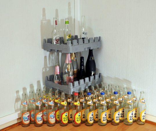 Lattialla Club-Mate-virvoitusjuomapulloja, niiden päällä kennolevy, sen päällä kolme isoa ja kolme pientä Freixenet-kuohuviinipulloa, niiden päällä kennolevy, sen päällä Sol-olutpullo, Somersby-siideripullo ja Corona-olutpullo.