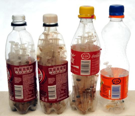 Neljä muovipulloa, joiden sisällä on paljon injektioruiskuja.