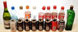 Lasipulloja sekä osittain avattuja muovipulloja ja juomatölkkejä, joiden sisäreunoilla näkyy tupakan jäämiä.