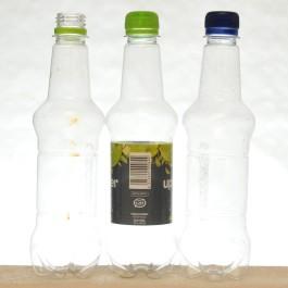 Kolme samanmuotoista muovipulloa, joista keskimmäisessä on etiketti.