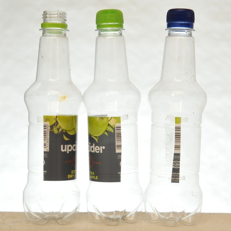 Vierekkäin kolme muovipulloa, joissa jokaisessa on kaistale samasta etiketistä.