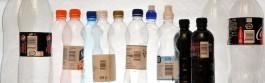 Vierekkäin etiketittömiä muovipulloja ja vastaavia etiketillisiä muovipulloja.