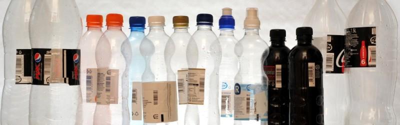 Vierekkäin muovipulloja, joissa on viivakoodin kohdalta puolitetut etiketit.