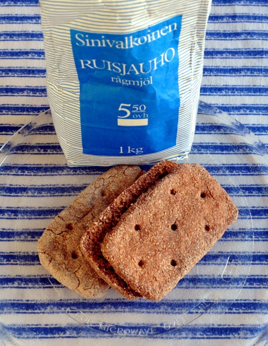 Kaksi ruispalaleipää mikron lasilautasella. Takana T-kaupan Sinivalkoinen-ruisjauhopussi ja taustalla sini-valkoraitainen kangas.