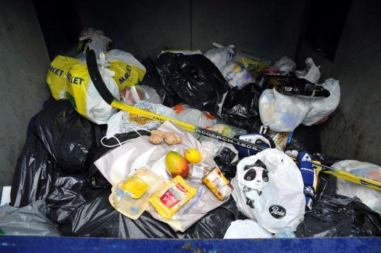 Isossa jätesäiliössä roskapusseja, elintarvikkeita ja jääkiekkomaila.