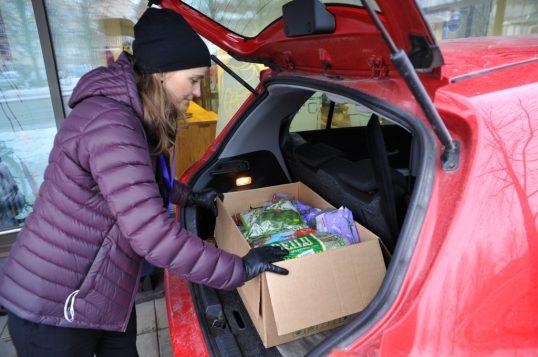 Heidi Uppa tarttumassa auton pienessä takakontissa olevaan pahvilaatikkoon, joka on täynnä elintarvikkeita.