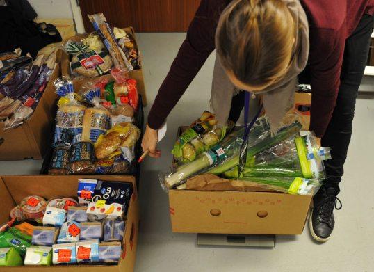 Heidi Uppa asettaa vaa'alle kasviksia täynnä olevan pahvilaatikon. Viereisissä laatikoissa maito- ja leipätuotteita.