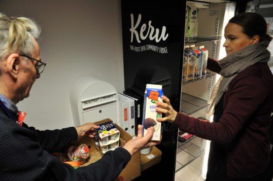 Mikael Lindström ojentaa jukurttitölkin jääkaappia täyttävälle Heidi Upalle.