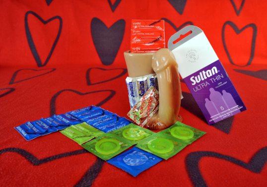 Punaisella sydänkuvioisella huovalla kondomipakkauksia ja muki, jossa on korvan asemesta penis.