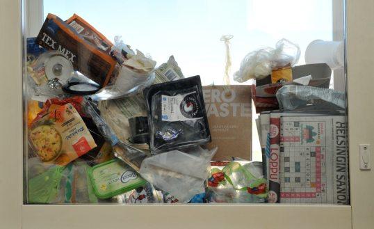 """Ikkunan välissä sanomalehtiä, tyhjiä elintarvikepakkauksia ja Zero waste -kirja, jonka otsikosta erottuvat sanat """"ero"""" ja """"aste""""."""
