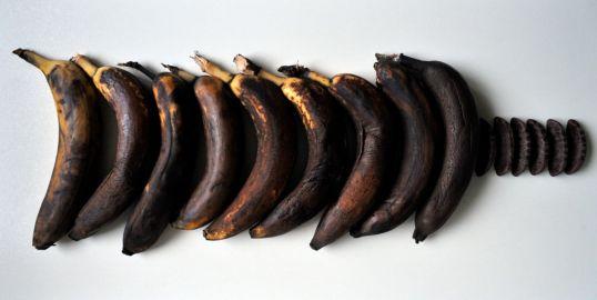 Tummuneita banaaneja vierekkäin suklaapäällysteisten banaanivaahtokaramellien vieressä.