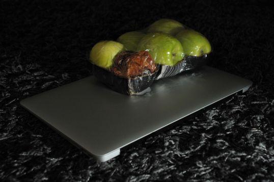 Macbook-kannettavan päällä rasia vihreitä omenoita, joista yksi on pilaantunut.