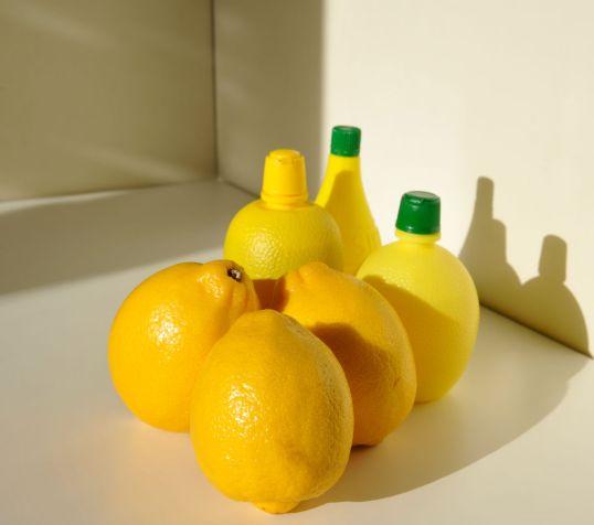 Sitruunoita ja sitruunamehupulloja auringonvalossa.