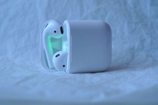 Applen langattomat Airpods-kuulokkeet avatussa latauskotelossa valkoista lakanaa vasten.