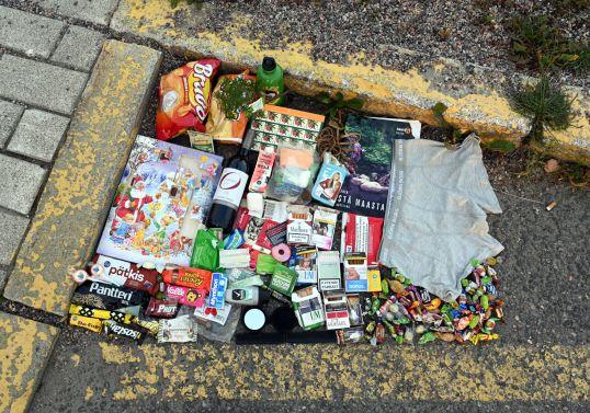 Kadulta löytyneitä tavaroita keltaiseksi maalattujen kadun ja reunakiveyksen rajaamalla alueella.