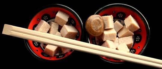 Tofukuutioita kahdella punaisella lautasella. Päällimmäisenä salmiakkiufo ja syömäpuikot.